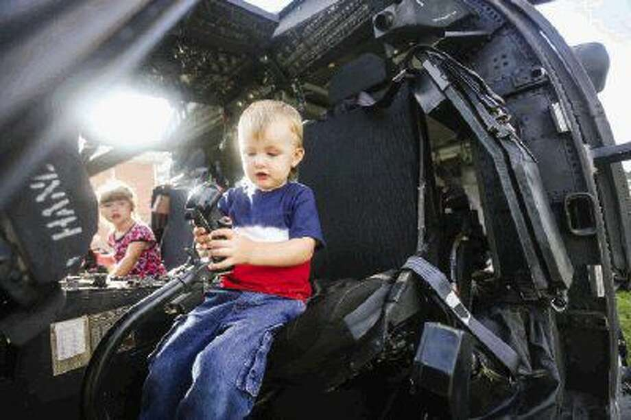 Bryson Debney, 2, and his sister Raelyn, 4, sit in the pilot seats of a UH-60 Blackhawk helicopter operated by the 1-158th Aviation Regiment during the Independence Day celebration on Sunday at West Conroe Baptist Church.