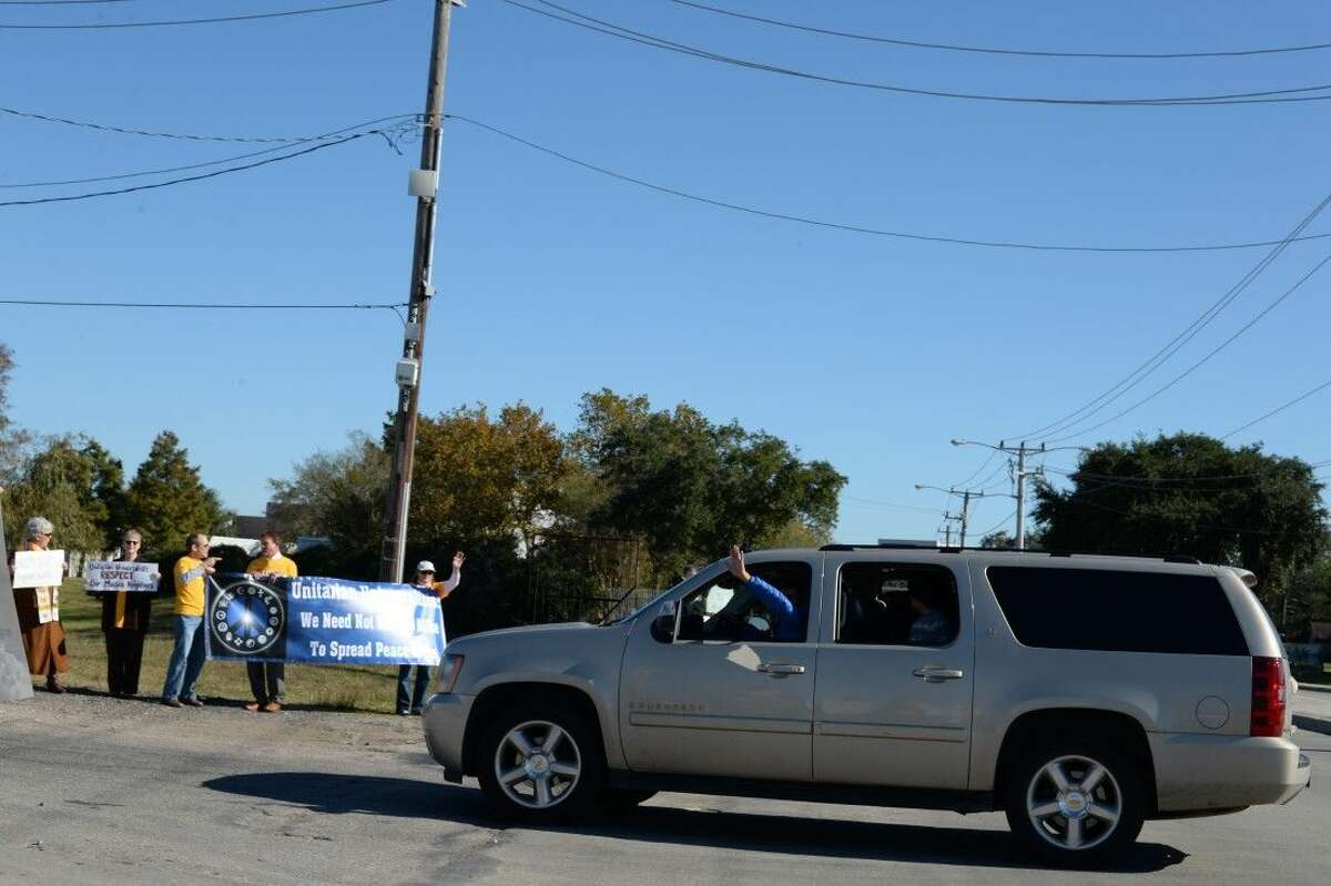 A member of the Clear Lake Islamic Center waves at the group as he arrives for Friday prayer.