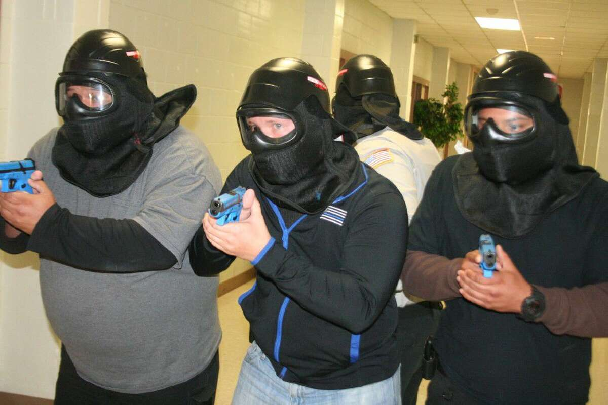 Armed with guns loaded with simunition, a four-man team made their way down the hallway of the school building to quell an active shooter situation Thursday, July 7, 2016.
