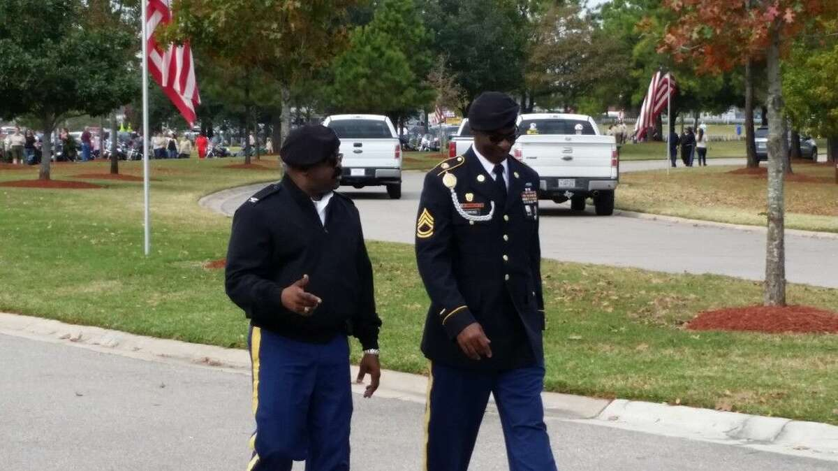 Men in military uniforms walk in Houston National Cemetery during Wreaths Across America Saturday