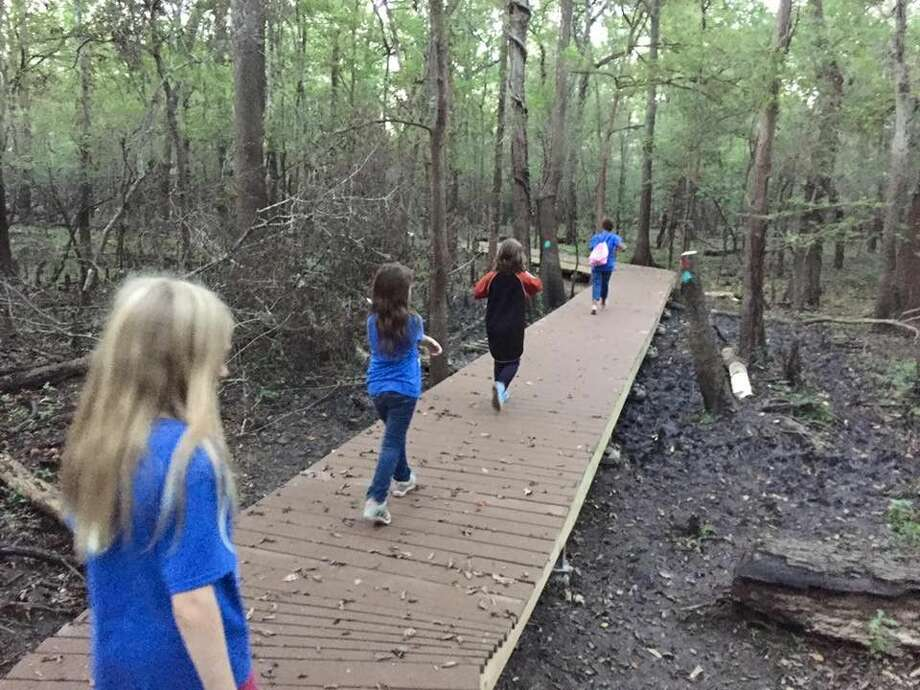 A group of children walk along a section of boardwalk in the Trinity River National Wildlife Refuge's nature trail that starts and ends at the city park in Liberty. Recent rains have the trail temporarily underwater. Photo: Trinity River NWR