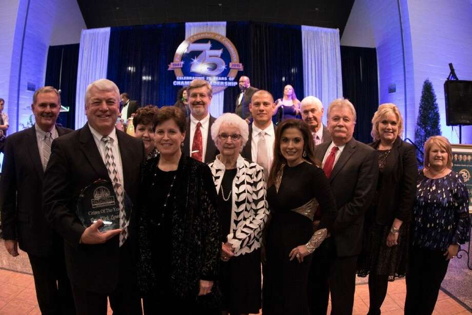 Dr. Kirk Lewis receives the 2015 Pasadena Chamber of Commerce Citizen of the Year award. From l to r (front row): Lewis with wife Robin; board assistant secretary Nelda Sullivan; board president Mariselle Quijano; board member Fred Roberts; deputy superintendent and incoming superintendent of schools Dr. DeeAnn Powell and executive assistant to the superintendent Debbie Smith. From l to r (back row): Pasadena ISD board member Jack Bailey; board vice president Vickie Morgan; associate superintendent of business and finance John Piscacek; board member Kenny Fernandez and board secretary Marshall Kendrick.