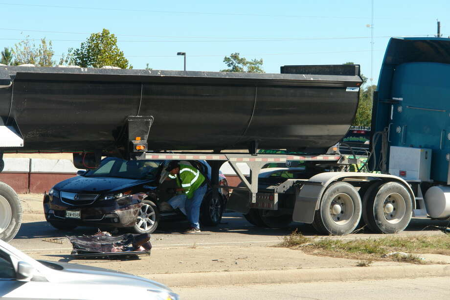 A emergency worker collects debris from a vehicle involved in an accident Wednesday on the on-ramp to State Highway 249 south of Spring-Cypress Road. Photo: Staff Photo By Roy N. Kent