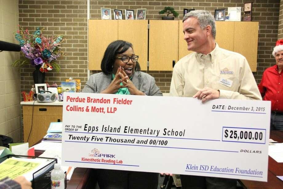 LaToya Wynne, principal of Epps Island Elementary, receives a $25,000 check from Perdue Brandon Fielder Collins&Mott, LLP on Thursday, Dec. 3.