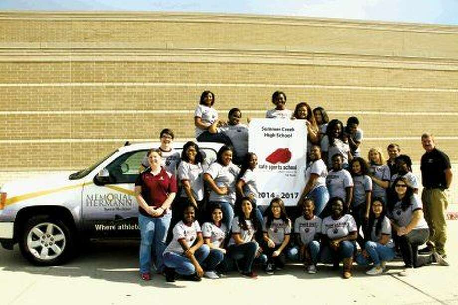 "Athletic trainers Sara Hansen, standing far left, and Brandon Rayne, standing, second from right, along with their Summer Creek High School student athletic trainers, display their ""Safe Sports School"" banner. Also pictured is Robert Maniscalco (far right), community outreach athletic trainer with Memorial Hermann Northeast Hospital."