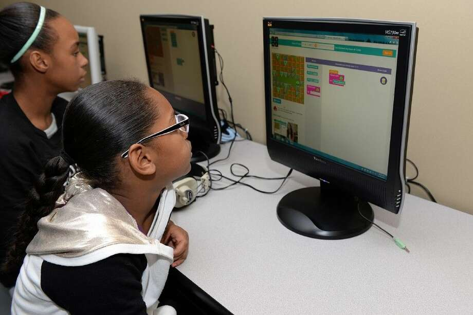 Hemmenway Elementary School fifth-grade students Sydnee Caesar, left, and Asia Dorsey participate in the Hour of Code on Dec. 8. Photo: Submitted Photo