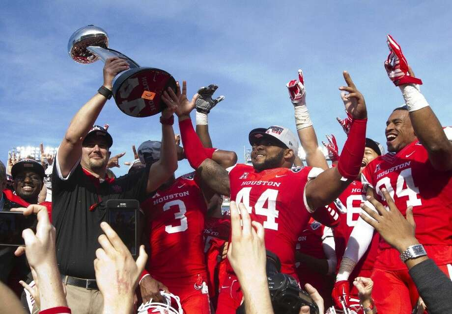 Houston head coach Tom Herman holds up the American Athletic Conference championship trophy after the Cougars defeated Temple 24-13 at TDECU Stadium Saturday, Dec. 5, 2015, in Houston. Photo: Jason Fochtman