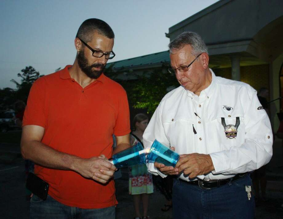 Liberty County Attorney-elect Matthew Poston (left) and Liberty County Sheriff Bobby Rader share a flame to light their candles at a vigil to support law enforcement on Friday, July 8, at Cleveland Police Department. The vigil, organized by the Cleveland Ministerial Alliance and led by Cleveland Fire Department Chaplain Lance Blackwell, was in response to the sniper killing of five police officers in Dallas the night before. Photo: Vanesa Brashier