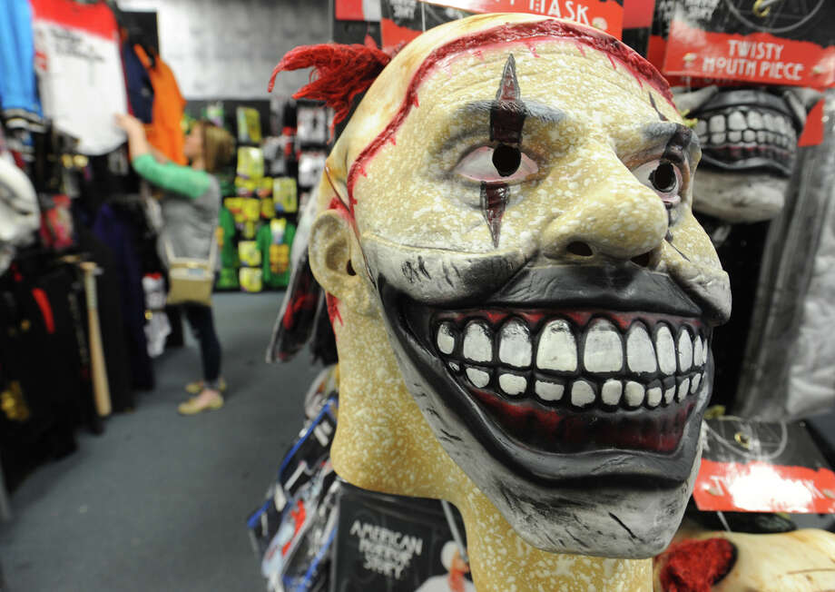 A clown mask hangs on a rack while Christie Farnham looks over costumes at Spirit Halloween in Beaumont on Wednesday.  Guiseppe Barranco/The Enterprise Photo: GUISEPPE          BARRANCO / B