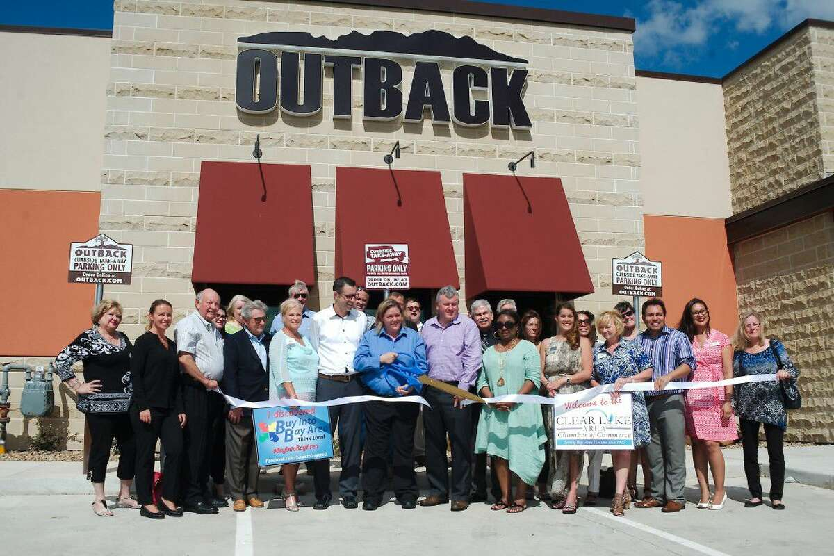 Members of the Clear Lake Area Chamber of Commerce stand by as Managing Partner Amy Fogarty cuts the ribbon to dedicate Outback Steakhouse on Bay Area Blvd near Baybrook Mall during a ceremony Wednesday, July 6.