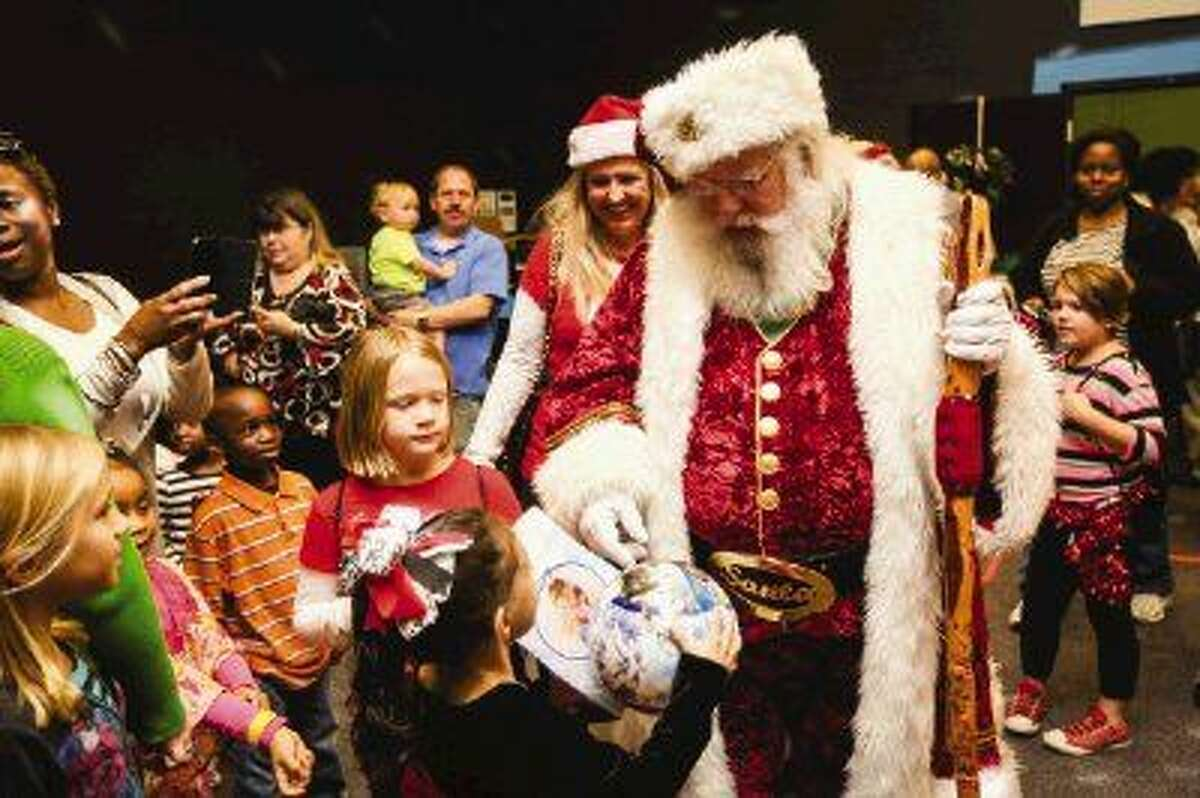 Light of Hope Community Legacy Award recipient Jim Fletcher, above as Santa Claus, brings joy and smiles to children during a Christmas celebration for foster children on Dec. 13 at WoodsEdge Community Church in The Woodlands.