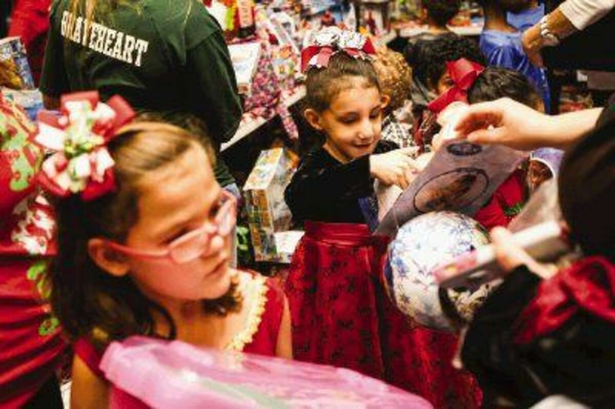 Jessica Rivera, 6, and Destiny Carpenter, 8, receive gifts during the Christmas for Foster Children on Saturday at WoodsEdge Community Church in The Woodlands.