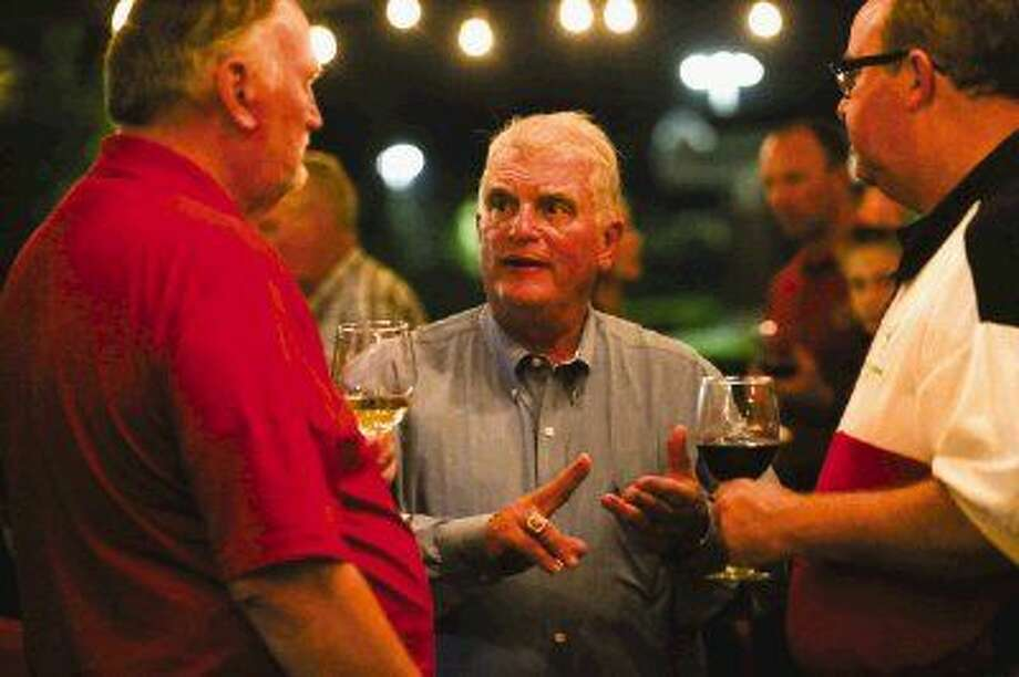 Mike Bass, running for re-election to Position 2 on The Woodlands Township board, speaks to supporters Kenny Speight, Texas Conservative Tea Party board member, left, and Steve Berry, of Waste Connections, right, during his election party Tuesday night at La Trattoria Tuscano in The Woodlands.