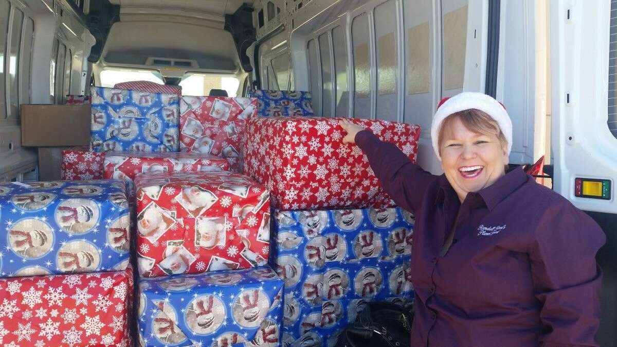 Kristi Williams of Planet Ford in Humble works to unload the boxes full of sweatshirts for students at Planet Ford in Humble on Dec. 16, 2014.