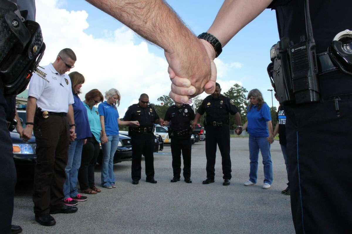 In this file photo, Cleveland police lock hands in prayer at a memorial service held last August for Harris County Sheriff's Deputy Darren Goforth. Since then, a second memorial service has been held for the five Dallas police officers killed by a sniper.