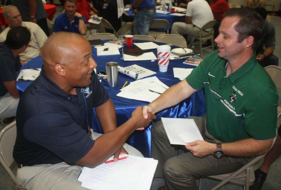 """Sam Rayburn head football coach Shaun Wynn and Clear Falls' top man shake hands after agreeing on the officiating crew they want for their Sept. 10th contest during Tuesday morning's """"Selection Day."""" Photo: Robert Avery"""