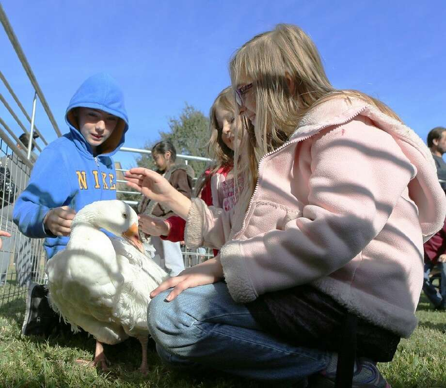 Children pet a duck in a petting zoo during Breakfast with Santa on December 5.