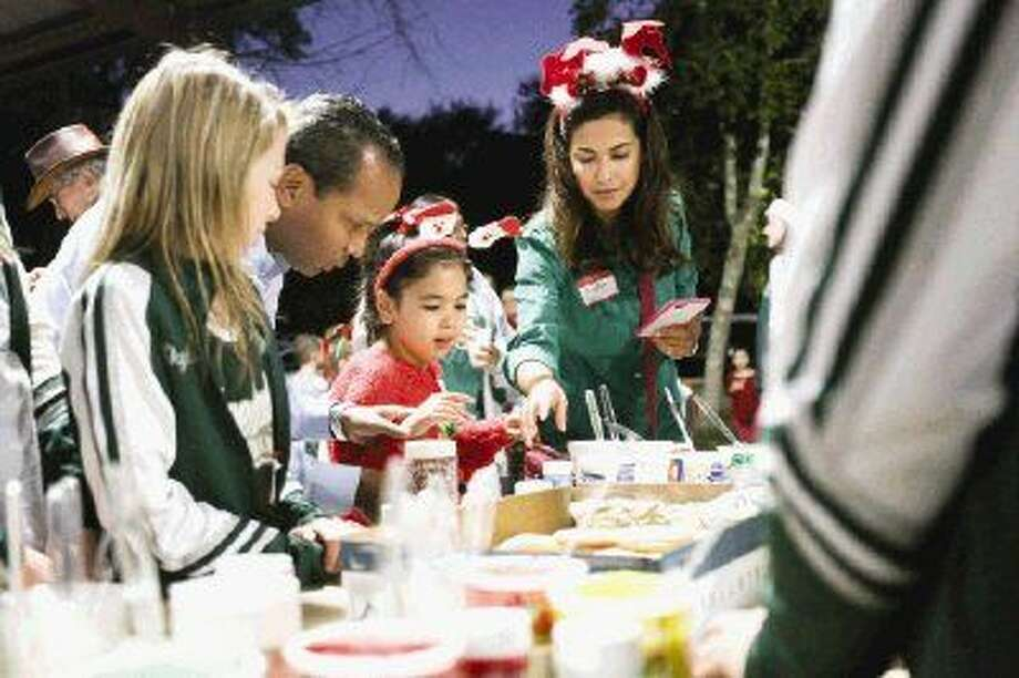Walter and Jennifer Sanchez help their daughter Sophia, 9, decorate cookies with the Knox Junior High School cheerleaders during the annual Panther Creek Inspiration Ranch Christmas Party on Monday. Photo: Michael Minasi