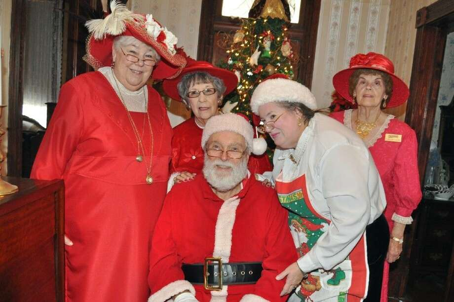Santa Claus is on hand at the annual Heritage Park Open House. Pictured from left are Rosie Richards, Eva Goulding, Lucy Turoff and Catherine Carlisle.
