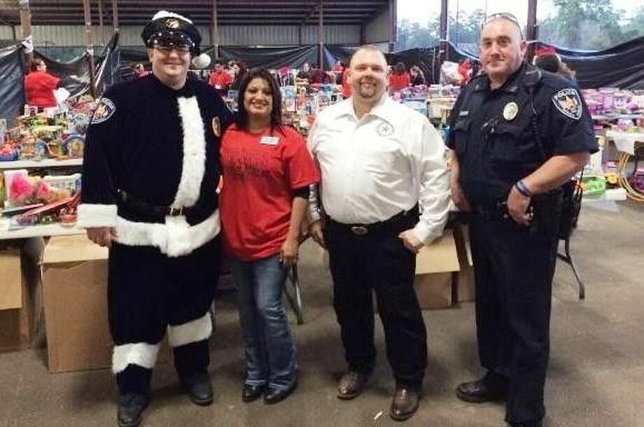 Lanora Purvis (second from left), founder of Heaven's Army, poses with members of the Roman Forest Police Department, including their own Sgt. Claus and Chief Stephen Carlisle, during Operation Giving Heart.
