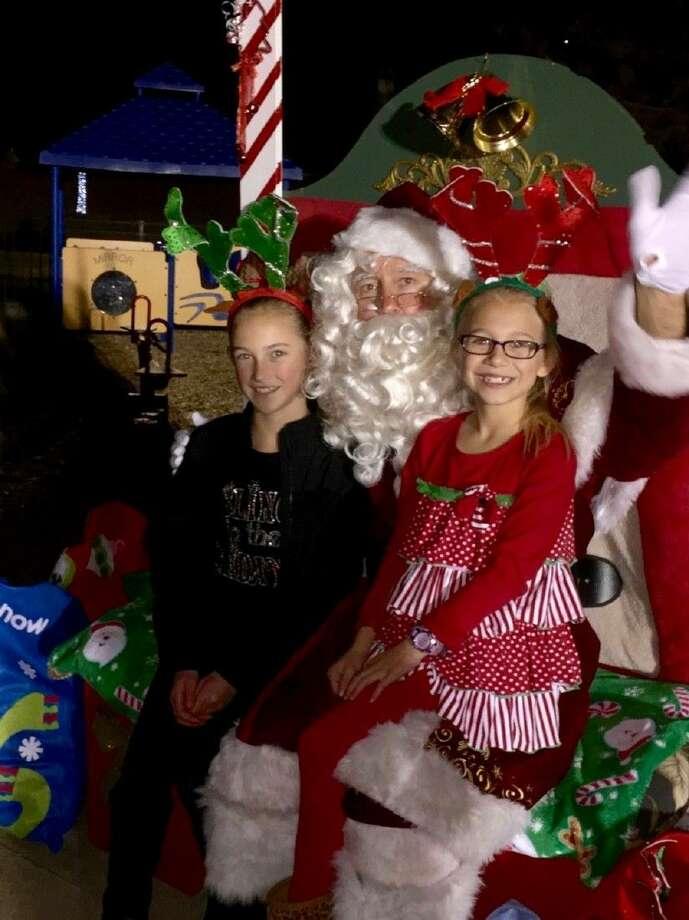 Hailey and Tori Prodan tell Santa what they want for Christmas. (Photo by Natasha Prodan).