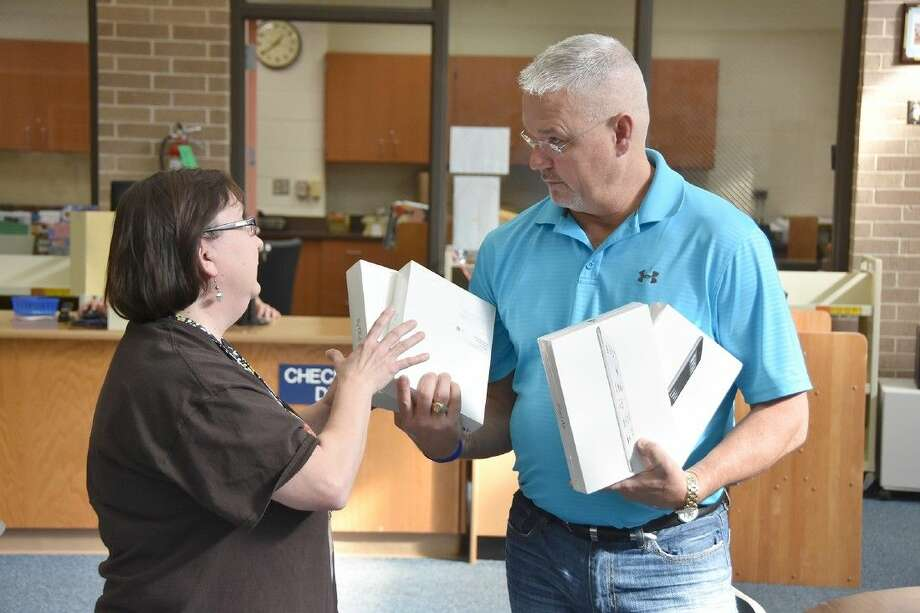 Robert Partin, vice president of the Stone Gate Home Owners Association, presents four iPads to Wilson Elementary School librarian Theresa Rogalski on Dec. 7.
