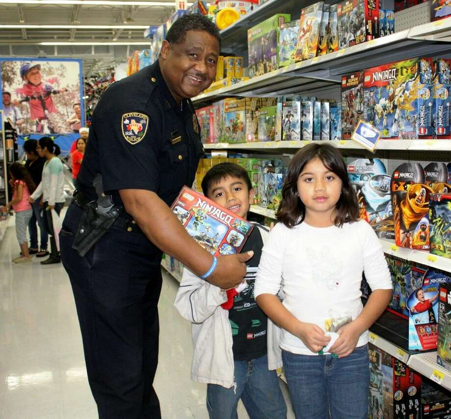 Cleveland Police Department Chief Darrel Broussard participates in the Shop with Cops event at Cleveland Walmart on Friday, Dec. 11. He helped children, including Alexia and Leonardo, pick out toys with a $50 gift card provided by the store and organized by Minister Juanita Lewis of Resurrection Ministry. Photo: Stephanie Buckner