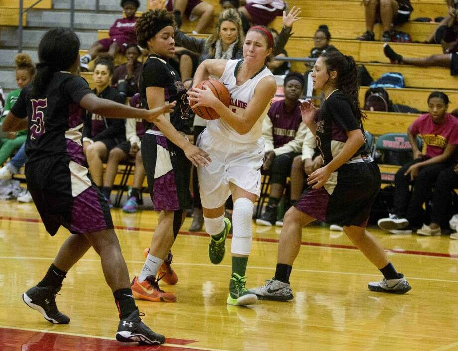 The Woodlands forward Payton Walker drives to the basket through a double team during the first half of a girls basketball game Friday in The Woodlands.