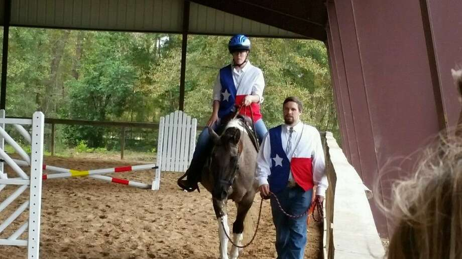 A member of the Lake Houston Hurricanes Special Olympics team and her coach walk a horse at the Kingwood Equestrian Center's course Saturday, Dec. 12, 2015.