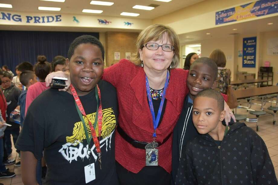 "Dr. Carrie Marz, Bane Elementary School principal, joins (L-R) Wendell Levi, Ashton Williams and Timmie Baker after ""The Gift"" announcement for fourth-grade students during the Dec. 9 lunch period."