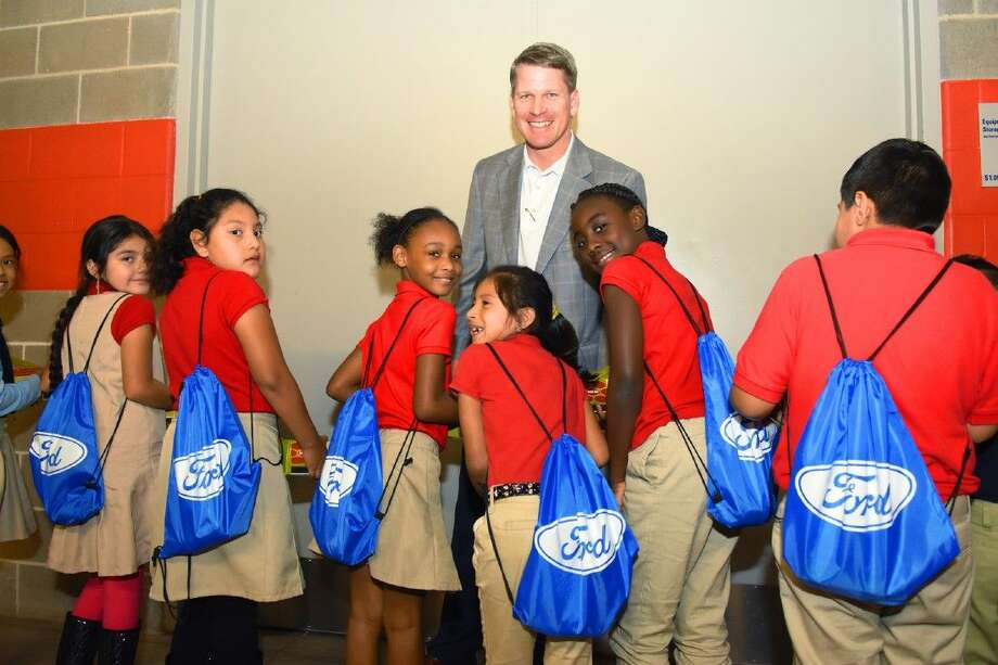 Students from Shearn Elementary and Tomball Ford general manager Brent were all smiles after receiving their new books and backpacks on Tuesday, Dec. 8, at the reading party held at the NRG stadium.