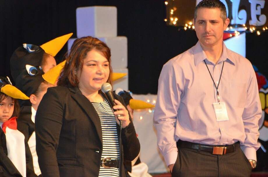 Frazier Elementary School principal, Gloria Vásquez, thanks the members of Faith Assembly Church for providing bicycles for every Frazier student during service on Dec. 14. Photo: Submitted Photo