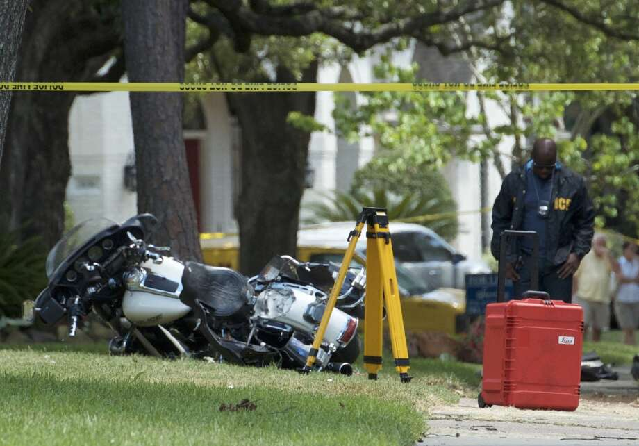 Investigators work the scene where a Bellaire Police Department officer died in a crash while pursuing shoplifting suspects. Photo: By Jay R. Jordan