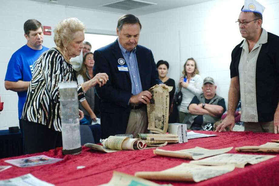 Kemah Mayor Carl Joiner, center, and Fiftieth Anniversary Celebration Executive Committee member Joann Blackledge, left, examine the contents of a time capsule buried in 1976 and retrieved as part of the Kemah 50th Anniversary Celebration Thursday, Dec. 10.