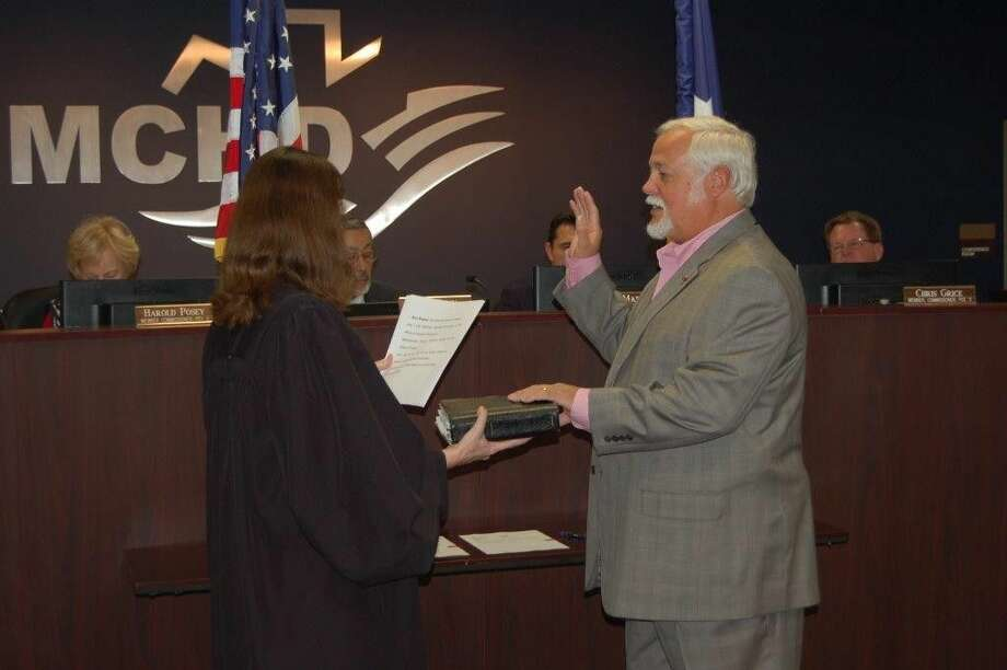 MCHD Commissioner of Precinct 3, Chris Grice, being sworn by County Court at Law 2 Judge Claudia Laird during the MCHD's special meeting on Thursday.
