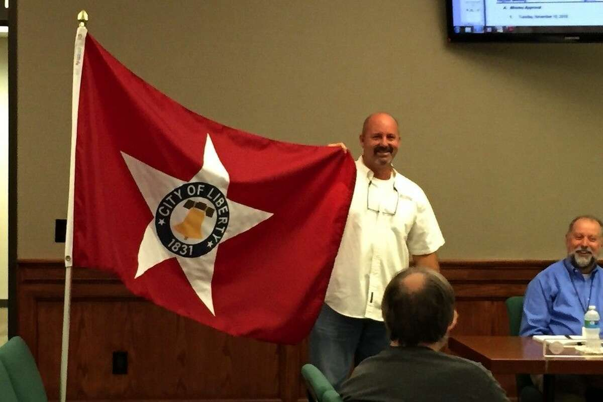 At the mayor's request Computer Solution's Randy Meche holds up the new City of Liberty flag for a photo.