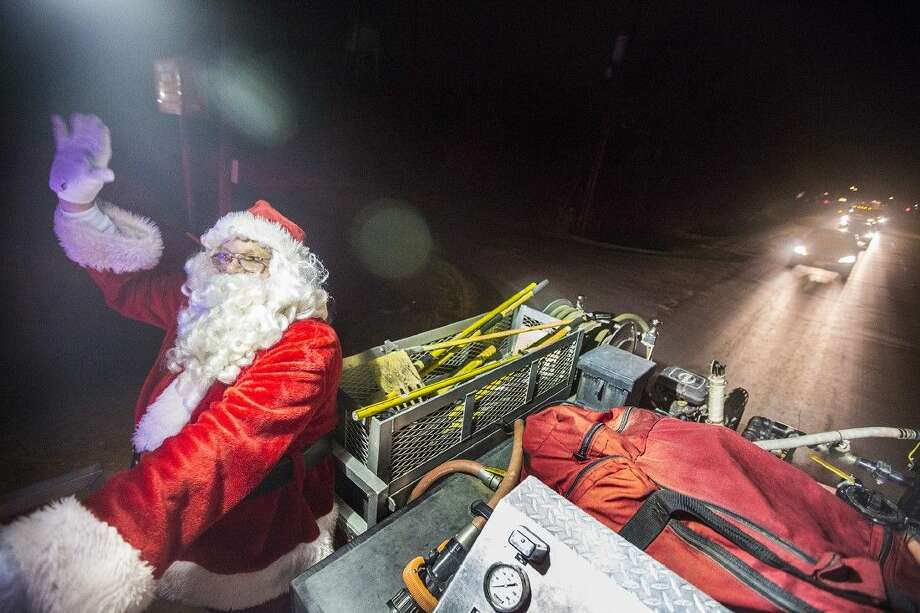 santa waves to passing cars while traveling up fm 2100 during the crosby volunteer fire departments