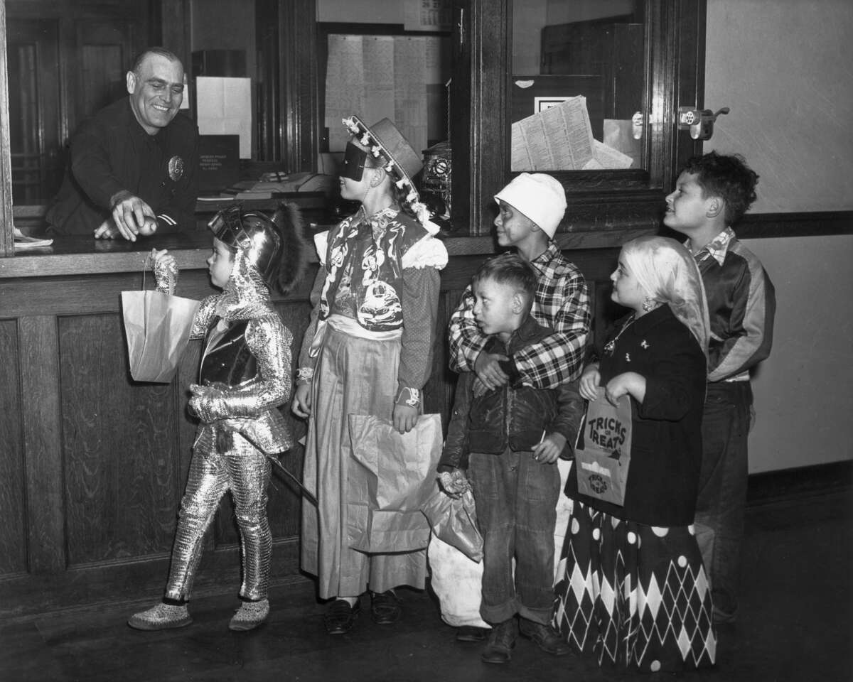 A group of children wearing Halloween costumes wait in a trick-or-treat line to receive apples from an officer at a police precinct. (Photo by American Stock/Getty Images)
