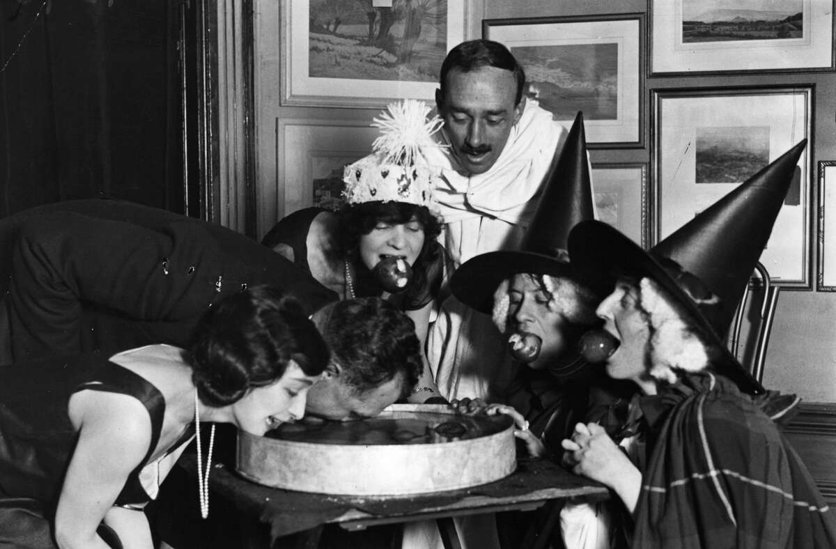 1922 Pictured: An apple bobbing game at a Halloween fancy-dress party.