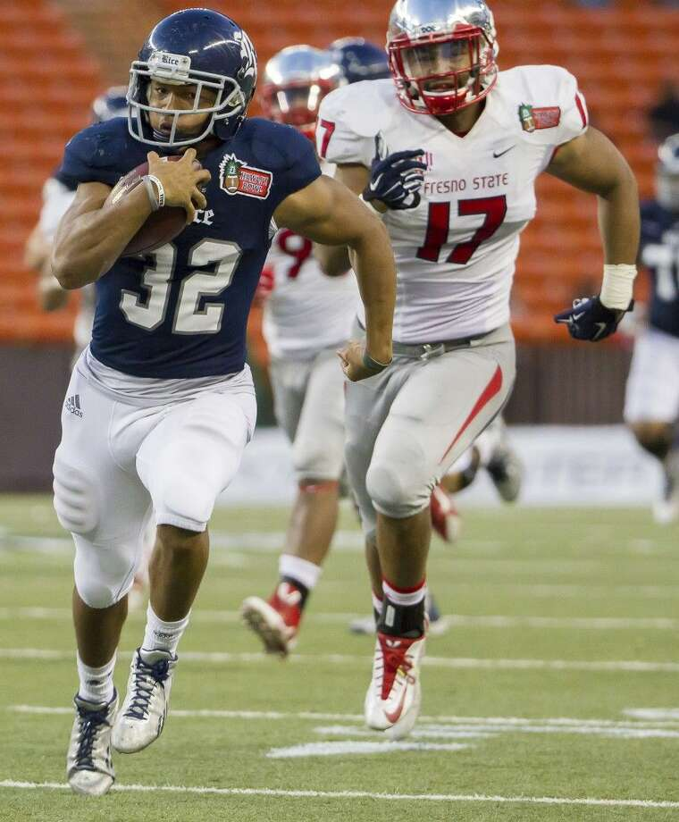 Rice's Darik Dillard, left, breaks away for a long run as Fresno State linebacker Kyrie Wilson gives chase late in the fourth quarter of the Hawaii Bowl. Rice won 30-6. Photo: Eugene Tanner
