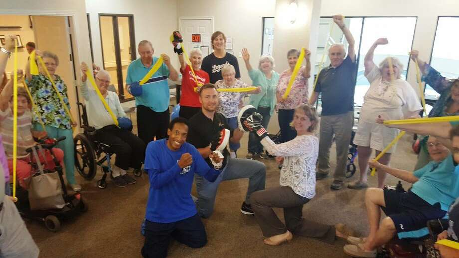 Arbor Terrace residents stand in their circle of trust around Boxercise coach Jay Robinson (center left,) sports therapy director Stuart Rutledge (center) and Arbor Terrace hospitality director Penny Reider (center right) as they use their newly donated exercise bands Thursday, July 14, in Kingwood.