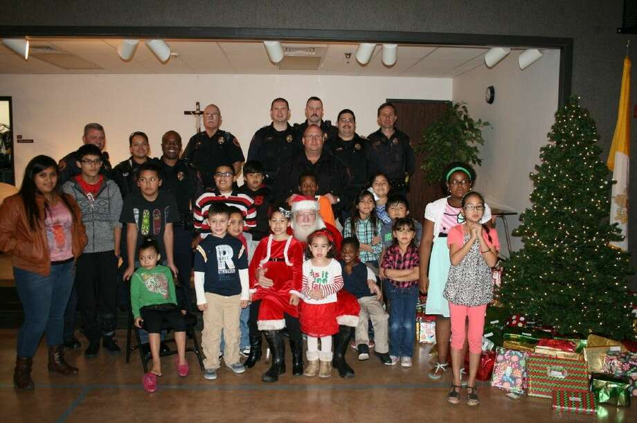 Pictured are Richmond Police Department officers along with the children at the Santa Behind the Badge event held at Sacred Heart Catholic Church Family Center in Richmond. The patrolmen helped children and their families have a joyful Christmas.
