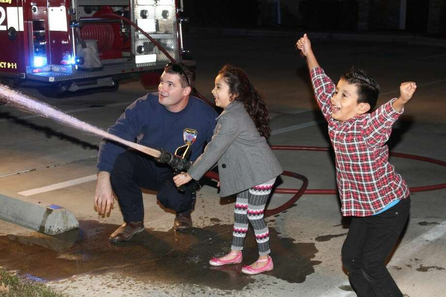 A gleeful child tries her hand at the fire extinguisher at the West I-10 Fire Department offices on Friday, Dec. 18. The department's annual toy drive provided gifts for families and children in need