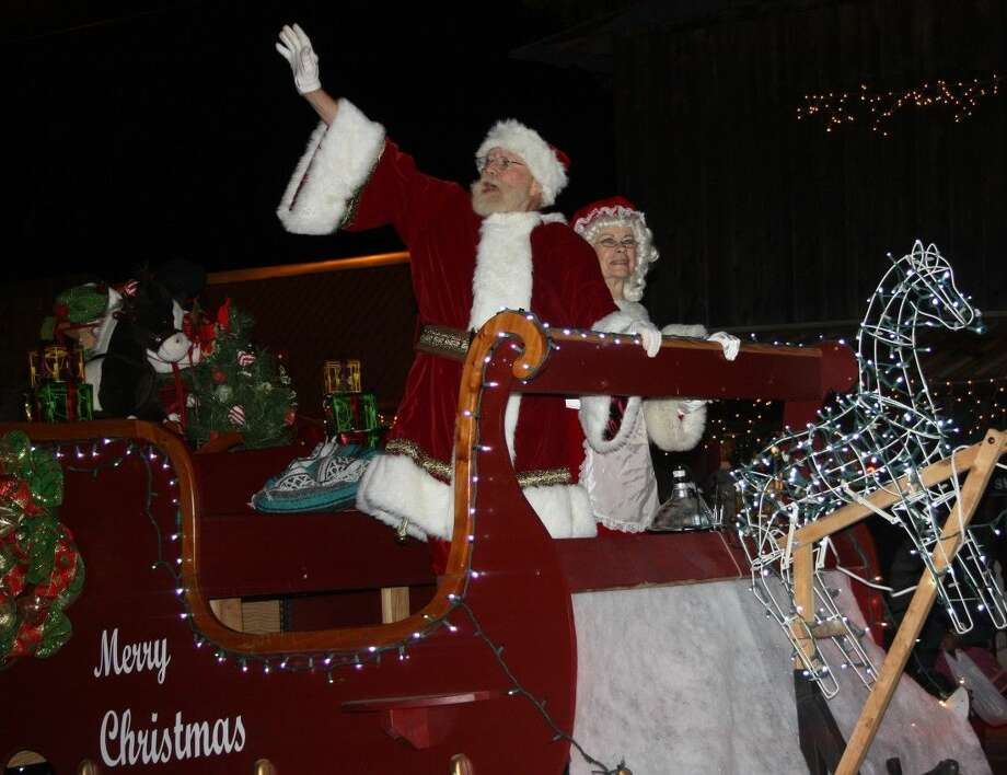 "The Christmas on the Square parade in 2014 marked the final year Robert ""Bob"" Jennings (left) portrayed Santa Claus before passing away in early 2015. He is riding upon his iconic sleigh, which he constructed along with Laddie McAnally as a more fitting float for St. Nicholas after previously riding atop a fire truck. Photo: Jacob McAdams"