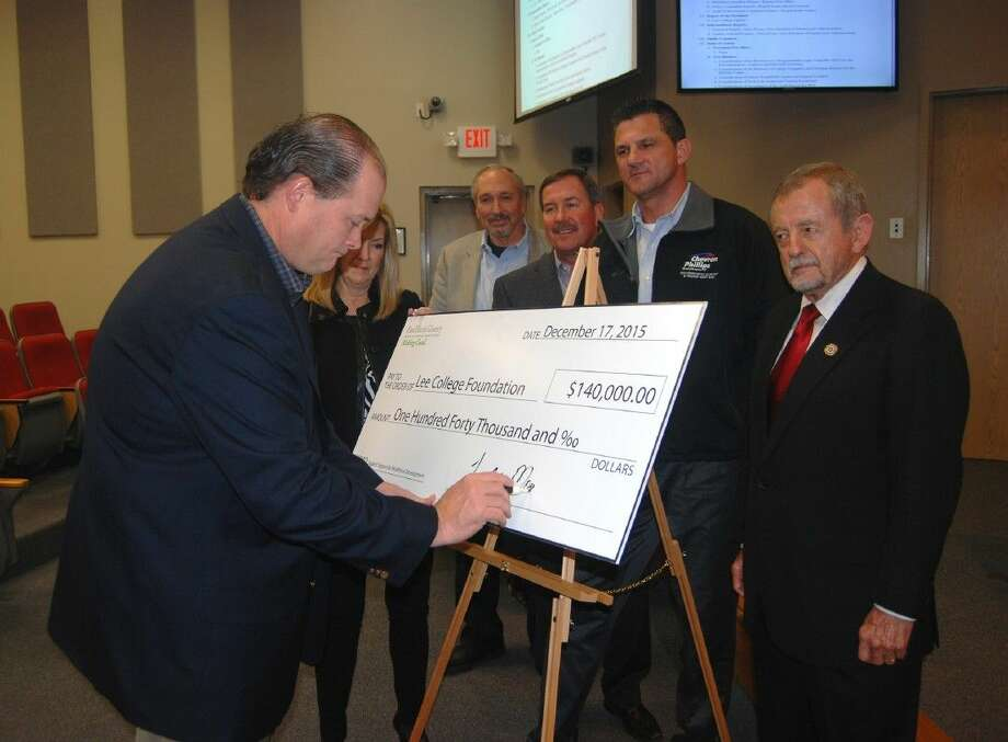 Todd Monette, outgoing Board Chairman for the East Harris County Manufacturers Association (EHCMA), signs a $140,000 donation check Thursday, Dec. 17, 2015, at the regular meeting of the Lee College Board of Regents. The association raised the money at its second annual golf tournament to provide scholarships and support for students in technical programs. Also pictured (l-r) are Pam Warford, Executive Director of the Lee College Foundation; Craig Beskid, EHCMA Executive Director; Monty Heins, incoming EHCMA Board Chairman; Roy Watson, Chairman of the EHCMA Workforce Development Committee; and Ronn Haddox, Chairman of the Lee College Board of Regents.