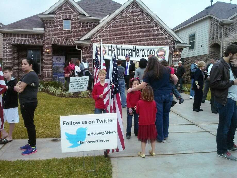 People gather outside the Eagle Springs home presented to Russ and Jackie Rodriguez and their four daughters by Helping a Hero on Monday, Dec. 21.