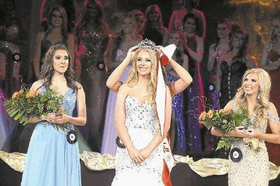 2016 Miss Tomball Hanna Carroll is crowned by 2015 Miss Tomball Julia Gimblet as Lauren Ysa, far left, and Kinsley Cantrell, far right, look on. The 50th annual pageant was held on Nov. 21 at Salem Lutheran Church. Photo: Tony Gaines