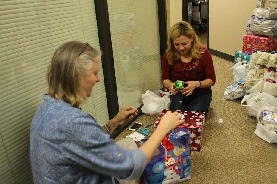 Voluteers wrap Christmas presents for seniors at Home Instead Senior Care Center- Northwest Houston. Photo: Taelor Smith
