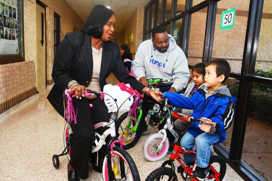 Bang Elementary School principal Erwann Wilson and former football star Rodney Hampton enjoy riding the new bicycles with two students Angelik Palomo and Adam Tran, who were rewarded bikes. Photo: Tony Gaines