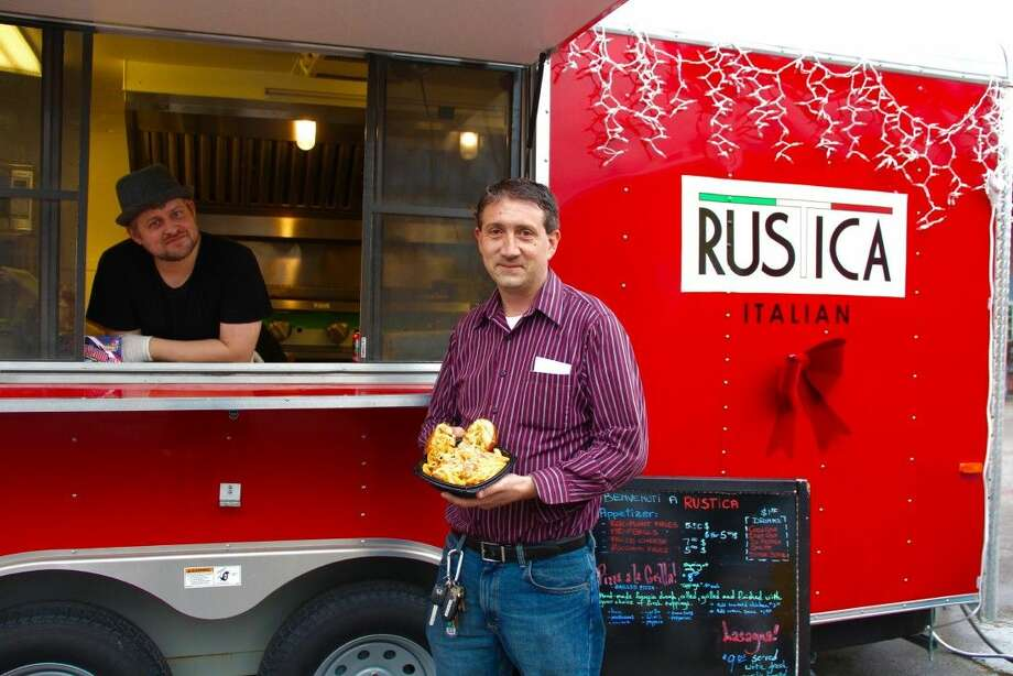 Matt Vernon, owner of the food truck Rustica Italian, holds one of the popular pasta dishes prepared by chef Timothy Ogden (pictured inside truck). Photo: Vagney Bradley